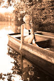 Woman relaxing on the vintage wooden boat. Thoughtful young blonde woman enjoying the sunny summer day on a vintage wooden boats on a lake in pure natural Royalty Free Stock Photos