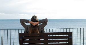 Woman relaxing watching ocean in a bench stock footage