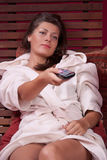 Woman relaxing and watching TV. Happy Caucasian woman relaxing and watching TV stock images