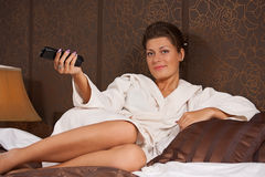 Woman relaxing and watching TV. Happy woman relaxing and watching TV royalty free stock photo