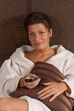 Woman relaxing and watching TV. Happy woman relaxing and watching TV royalty free stock photography