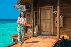 Woman is relaxing on the water bungalow of the tropical beach Royalty Free Stock Photography