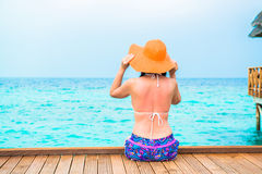 Woman is relaxing on the water bungalow of the tropical beach Stock Photography