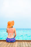 Woman is relaxing on the water bungalow of the tropical beach Stock Photo