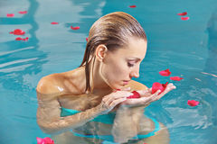 Woman relaxing in water with roses Stock Image