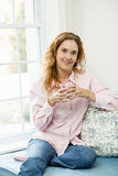 Woman relaxing by the window Stock Images