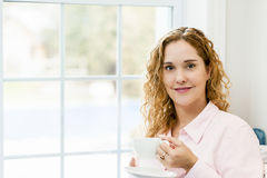 Woman relaxing by the window with beverage Stock Photos