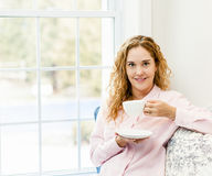 Woman relaxing by the window with beverage Stock Images