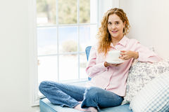 Woman relaxing by the window with beverage Royalty Free Stock Photography
