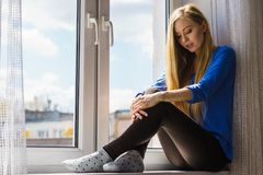 Woman relaxing on windowsill Stock Images