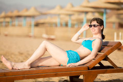 Woman relaxing on wooden lounger Stock Images