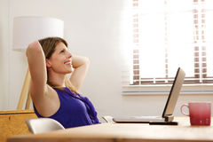 Woman relaxing at work with laptop. Side portrait of woman relaxing at work with laptop Royalty Free Stock Photo