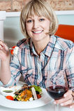 Woman relishing her meal with red wine Stock Image