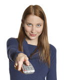 Woman with remote. Attractive young woman points remote control at viewer (focus on face Stock Photos