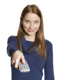 Woman with remote control. Attractive young woman points remote control at viewer (focus on remote control Stock Images