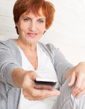 Woman with remote control Stock Photography