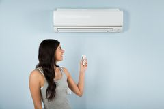 Woman with remote control of air conditioner Stock Images