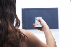Woman with remote control and flat tv. Woman and hand with remote control Stock Image