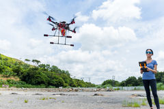 Woman with remote control and flying surveillance drone Stock Image