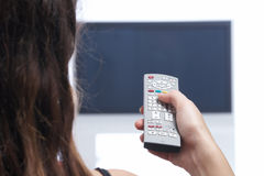 Woman with remote control in front of TV Stock Images