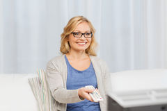 Woman with remote control switching tv at home Stock Image