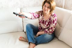 Woman with remote control from TV sitting on sofa Royalty Free Stock Images