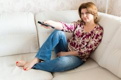 Woman with remote control from TV sitting on sofa Stock Photo