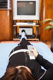 Woman with remote control watching TV. Middle aged woman with remote control watching TV at home. Shallow depth of field with focus on remote control Royalty Free Stock Photo