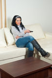 Woman with remote on couch Stock Image