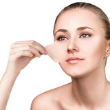 Woman remove her old dry skin from face. Royalty Free Stock Image