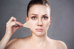 Woman remove her old dry skin from face. Beautiful woman remove her old dry skin from face. Over gray background Stock Images