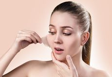 Woman remove her old dry skin from face. Beautiful woman remove her old dry skin from face. Over beige background Stock Image