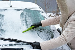 Woman remove snow from windshield Stock Photos