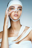 Woman removes the bandages from her head and touching her new face. Royalty Free Stock Images