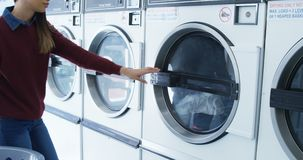 Woman removing clothes from washing machine 4k. Woman removing clothes from washing machine at laundromat 4k stock footage