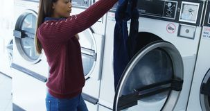 Woman removing clothes from washing machine 4k. Woman removing clothes from washing machine at laundromat 4k stock video