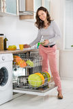 Woman Removing Cup From Dishwasher Stock Photo