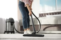 Woman removing dirt from carpet with vacuum cleaner at home. Closeup stock image