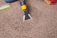 Woman removing dirt from carpet with vacuum cleaner in room stock image