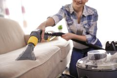 Woman removing dirt from sofa with vacuum cleaner stock images