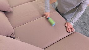 Woman removing dust and hairs from sofa with lint roller. In room stock video