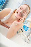 Woman removing facial clay mud mask in bathroom Stock Photo