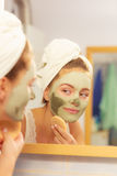 Woman removing facial clay mud mask in bathroom Royalty Free Stock Image