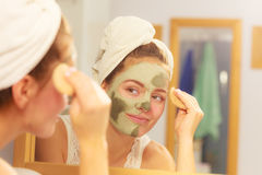 Woman removing facial clay mud mask in bathroom Stock Photos