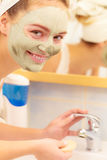 Woman removing facial clay mud mask in bathroom Royalty Free Stock Photos