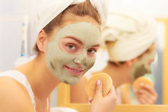 Woman removing facial clay mud mask in bathroom Royalty Free Stock Images