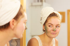 Woman removing facial clay mud mask in bathroom Royalty Free Stock Photography
