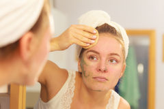 Woman removing facial clay mud mask in bathroom Stock Photography