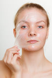 Woman removing facial peel off mask. Stock Photo