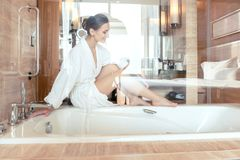 Woman removing hair by shaving her legs in bathroom of hotel. Sitting on the bathtub royalty free stock photo